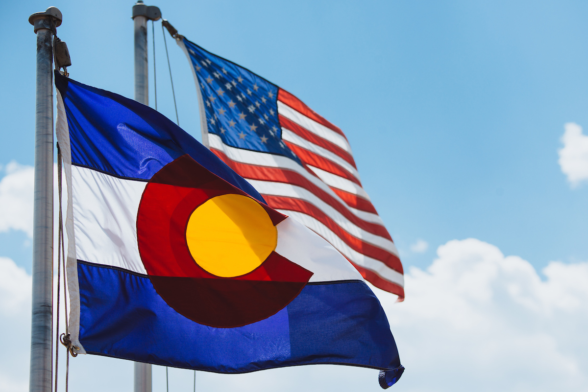 Colorado flag and american flag in the wind with blue skies in the background