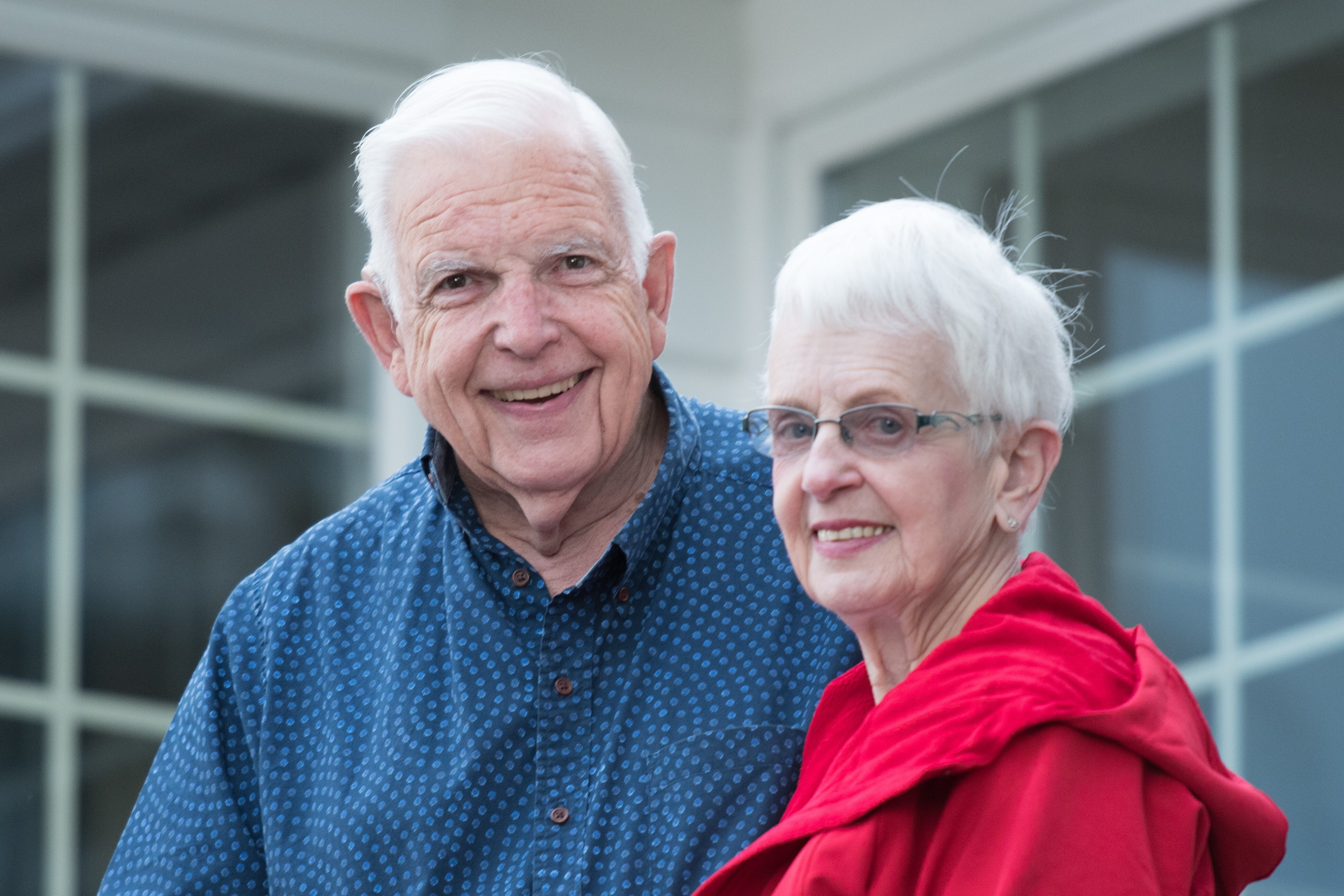 Color photo of older man in blue shirt and woman in red jacket. Both are smiling