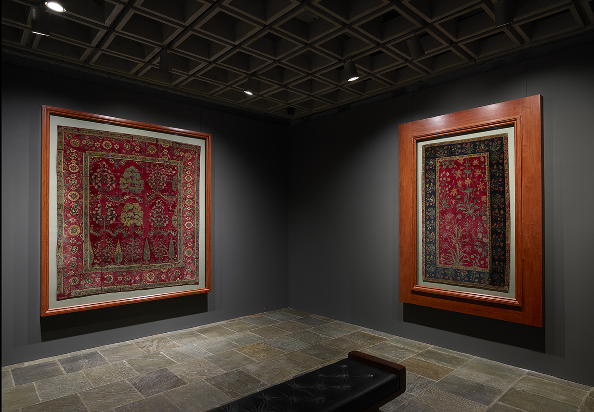 Installation view of two red carpets framed and hung on a gray wall