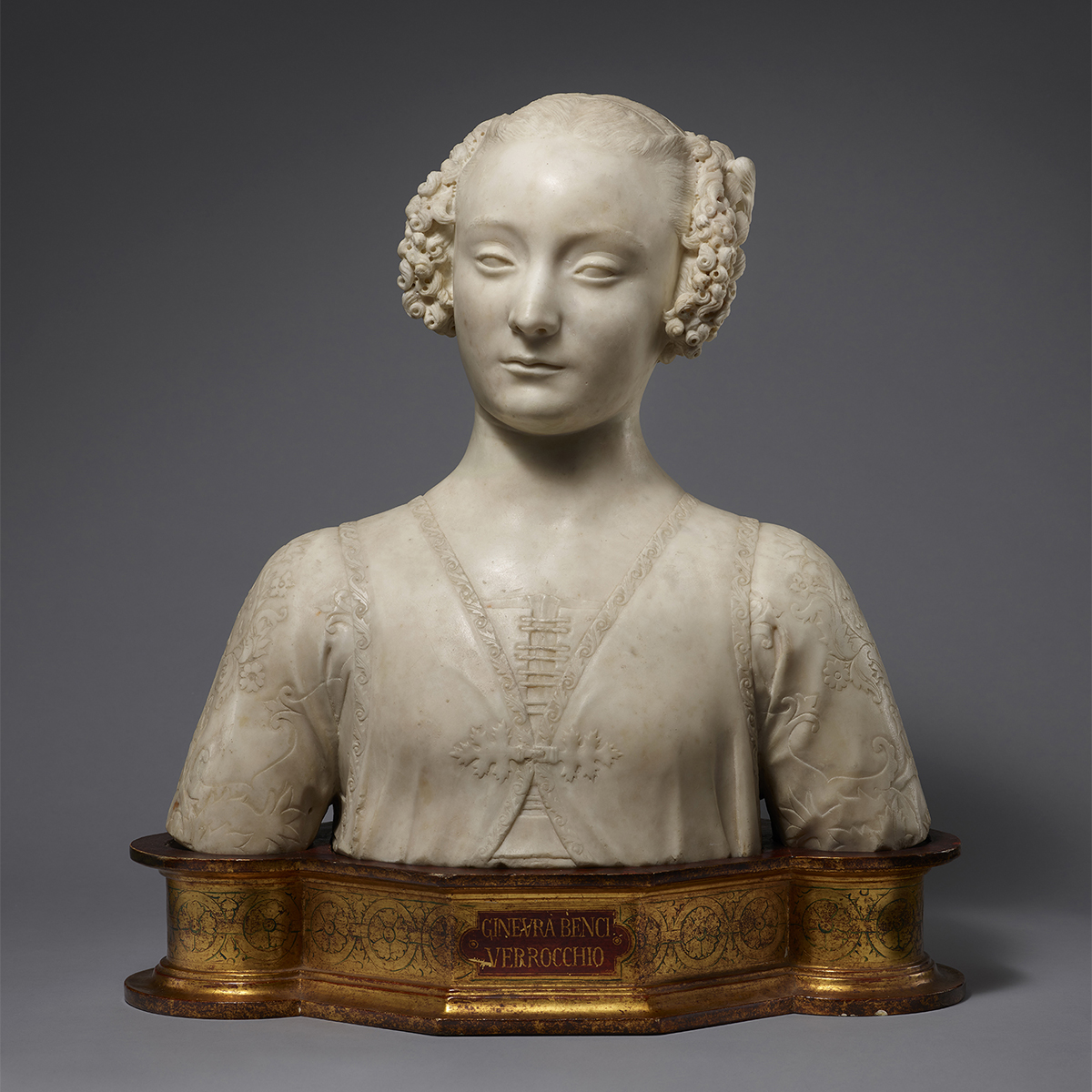 A marble bust of a young woman. Her curly hair is fastened with ribbons and rosettes. She wears a laced bodice