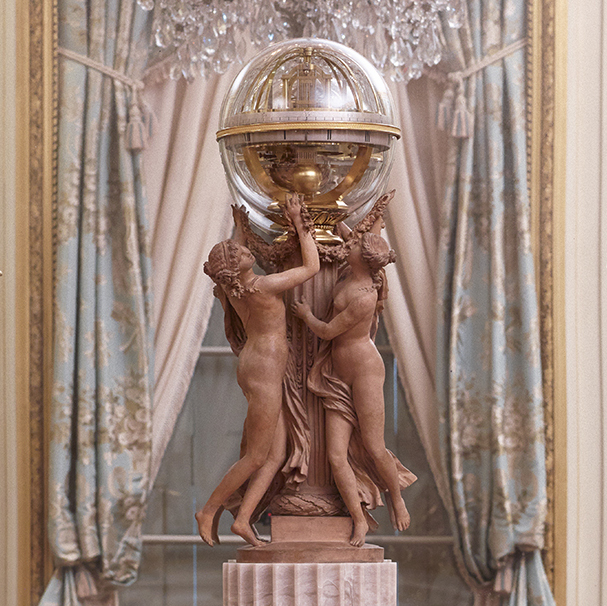 Terracotta sculpture of three nymphs supporting a glass orb containing a clock
