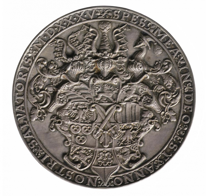 A silver medal with an engraving of a coat of arms