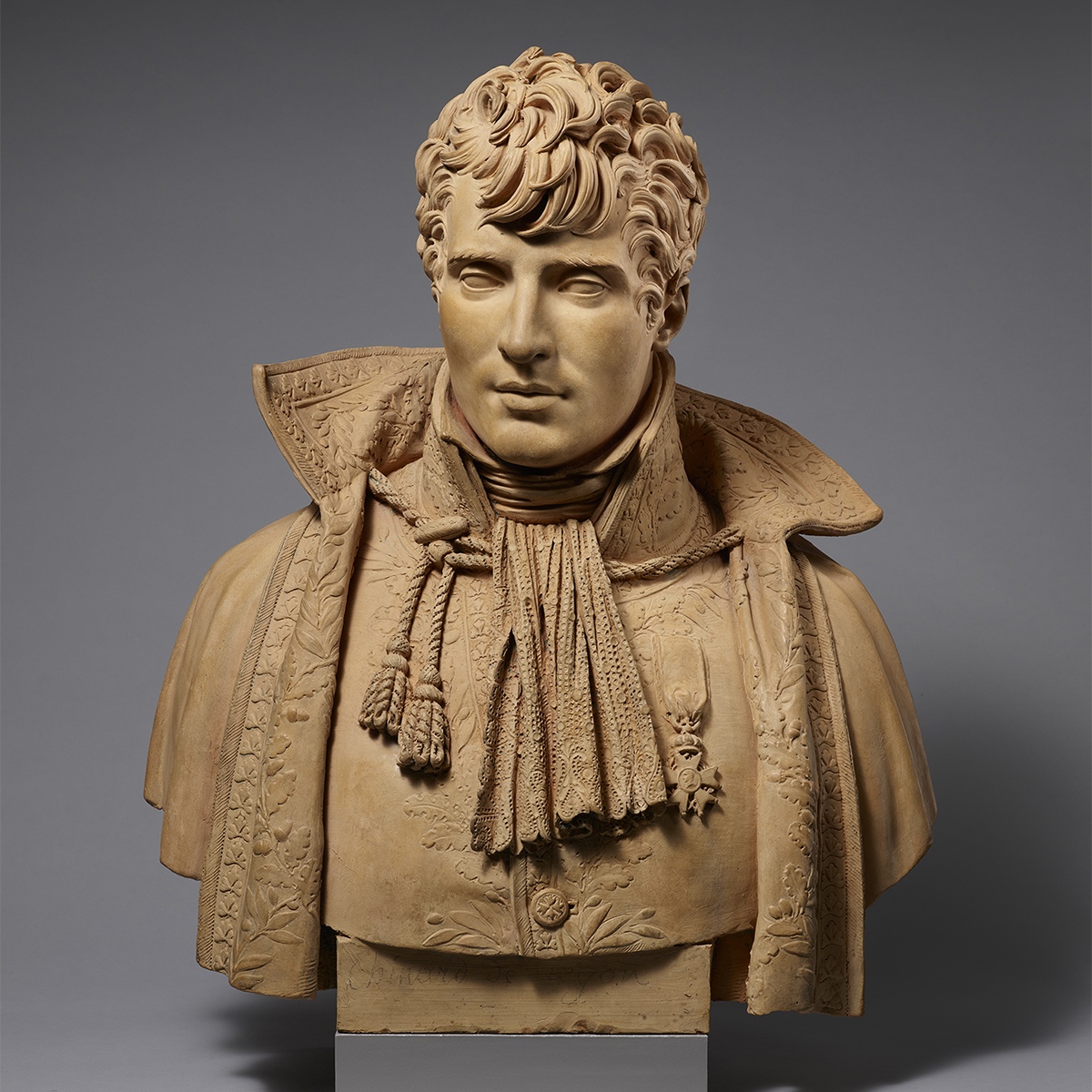 Terracotta bust of a man. He wears a high collared and detailed cloak, which has rope and tassels tied together around his neck