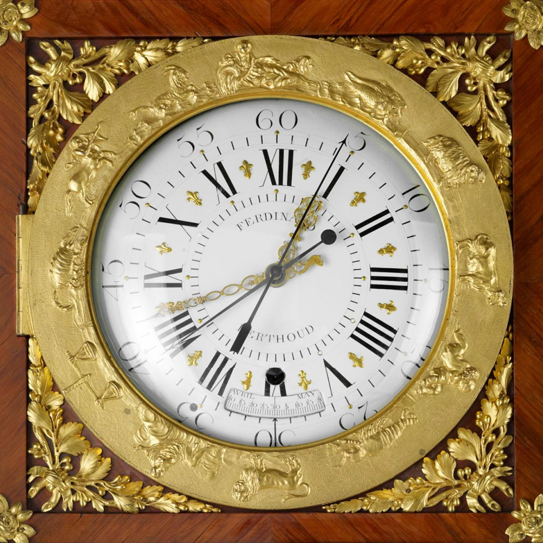 Ornamented clock face surrounded by a gilt bronze band decorated with reliefs of the signs of the zodiac, gold foliage, and a square wooden frame