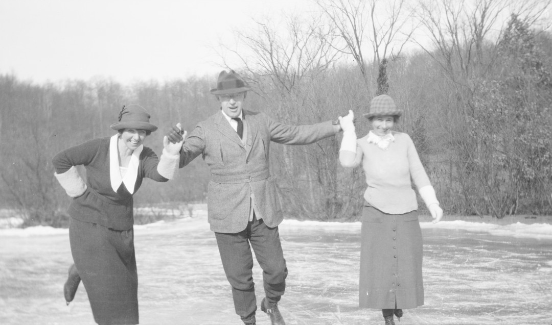 Black and white photograph from the 1920s of three people ice skating on a pond