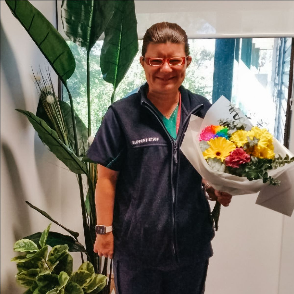 Jodie smiles as she holds a large bouquet of flowers