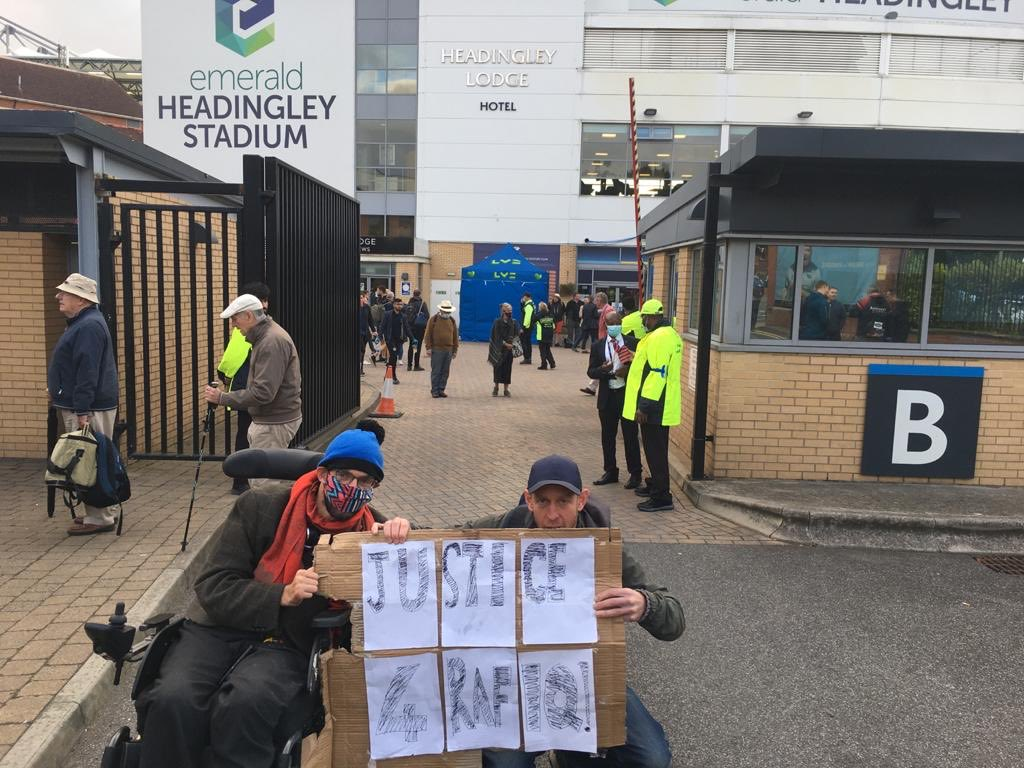 """Two people hold up a placard reading """"Justice for Rafiq!"""" outside of Headingley Stadium"""