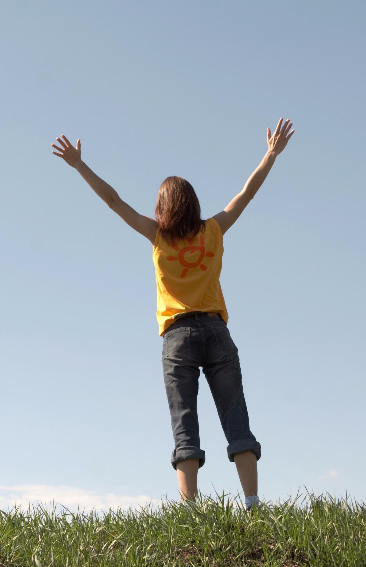 En ung person som sträcker armarna i luften