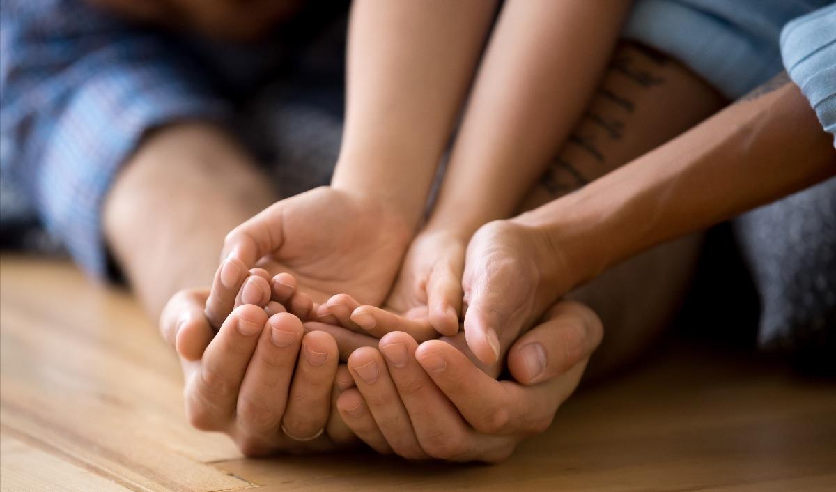Familj som håller varandras händer