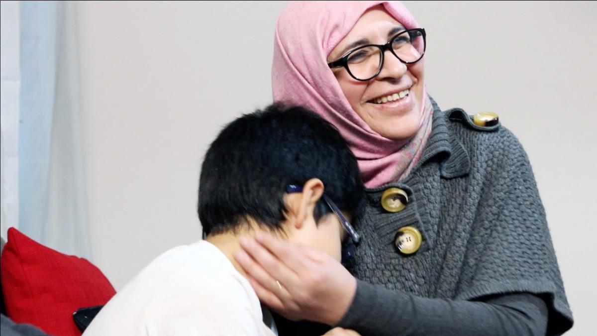 En kvinna som kramar ett barn