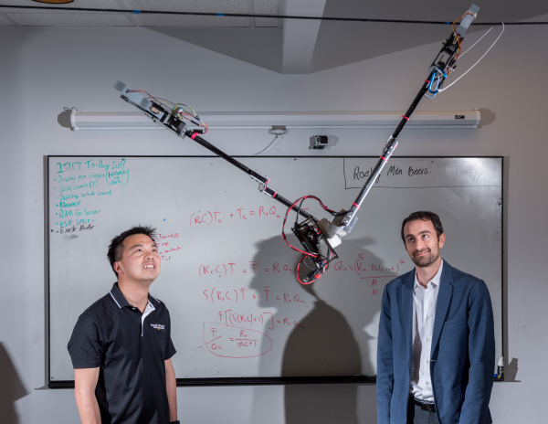 Tarzan-robot-swinging: Researchers Jonathan Rogers and Ai-Ping Hu are shown with the Tarzan robot in a Georgia Tech lab. The robot will swing from cables to inspect crops in the field. | Photo Credit: Jason Maderer, Georgia Tech