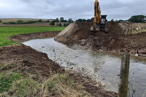 Digger backfilling the old river channel