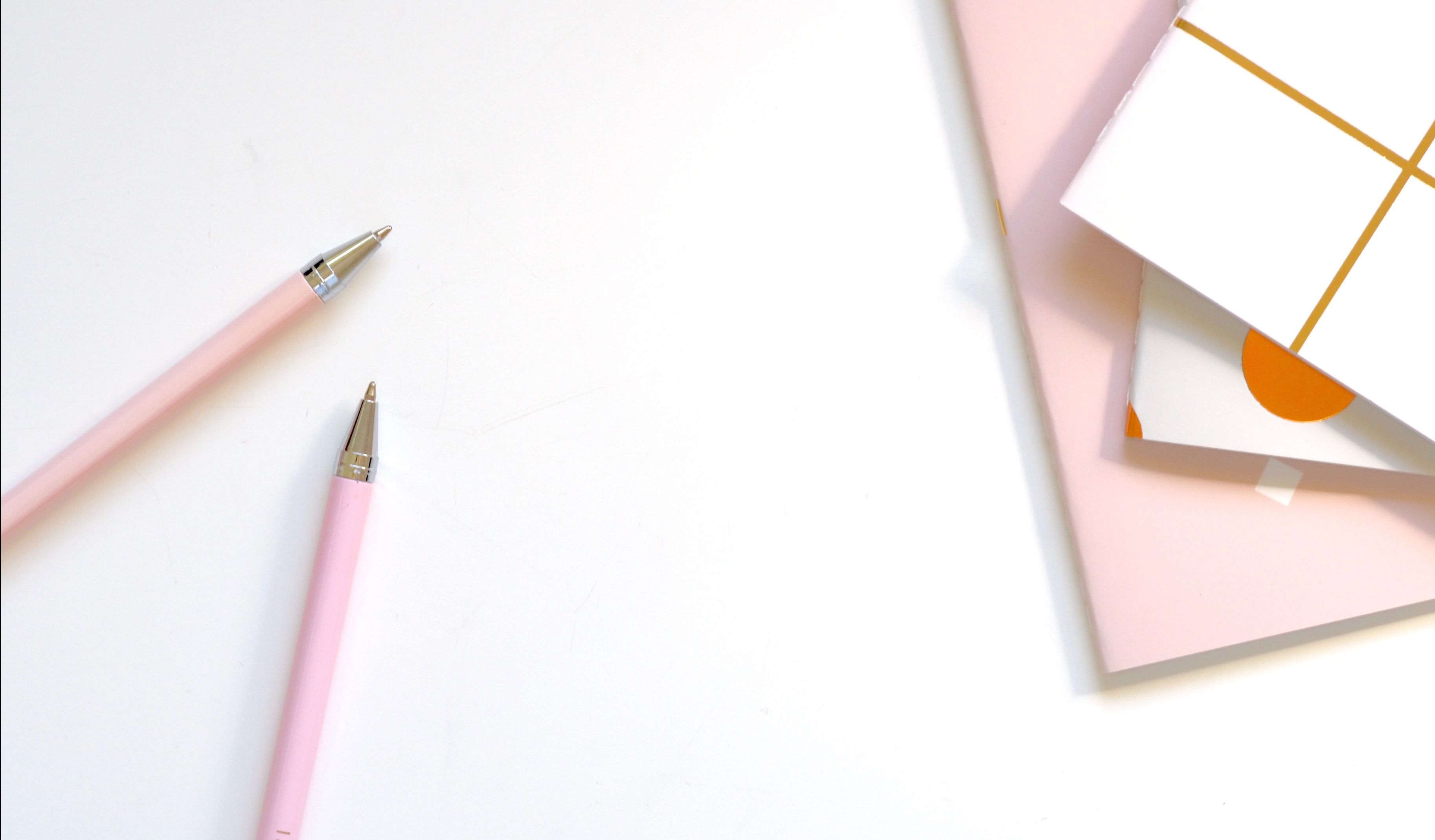 Pink notebooks and pink pins on a white desk.