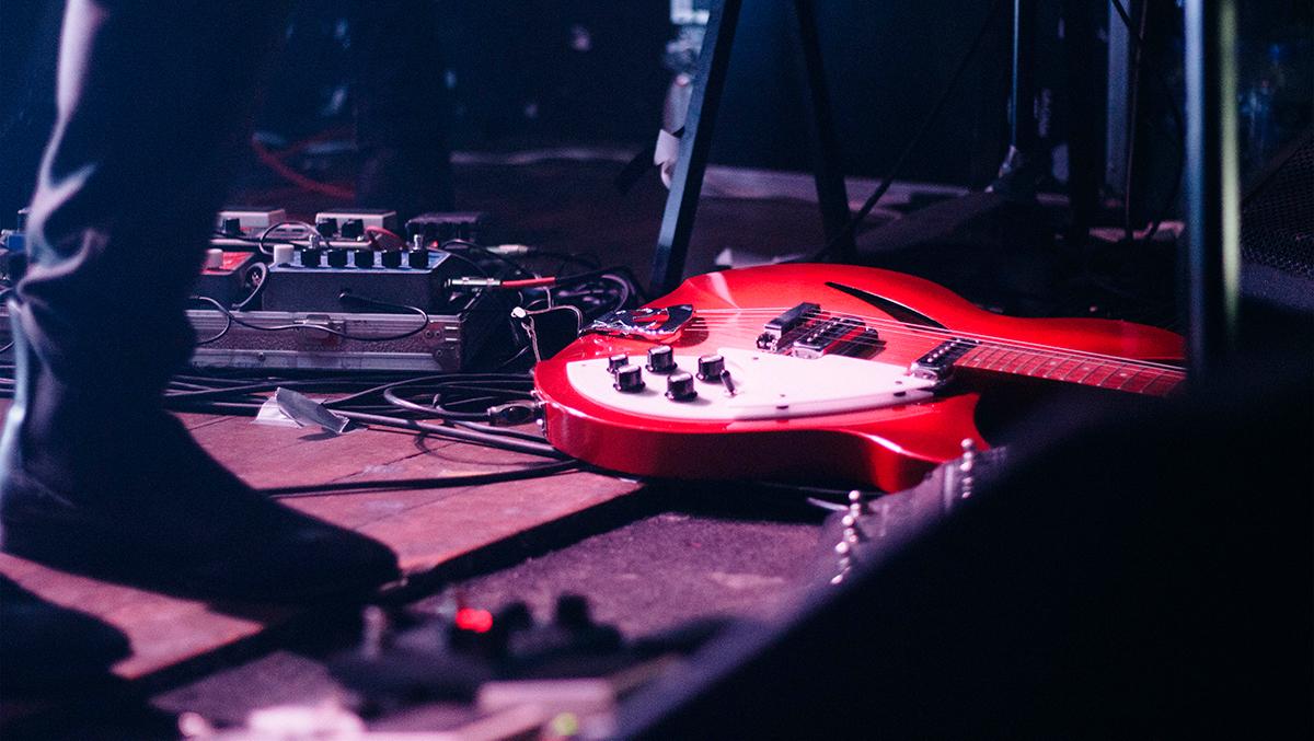 les pieds d'un guitariste avec sa guitare et ses pédales d'effets