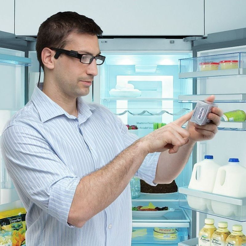 Man standing at fridge reading philly cheese label with OrCam Read device