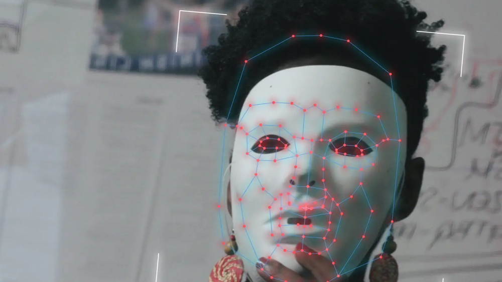 Image of a black woman wearing a white mask with red dots identifying the face.