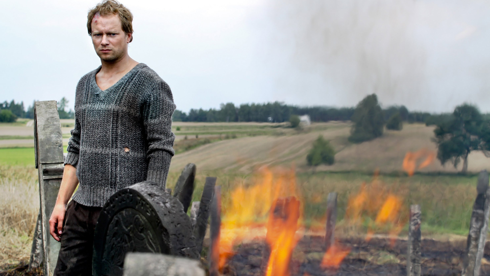Image of a blond man in front of fields with flames flickering next to him,
