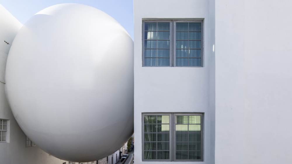 Image of a two-story egg shaped orb between two white buildings.  No words