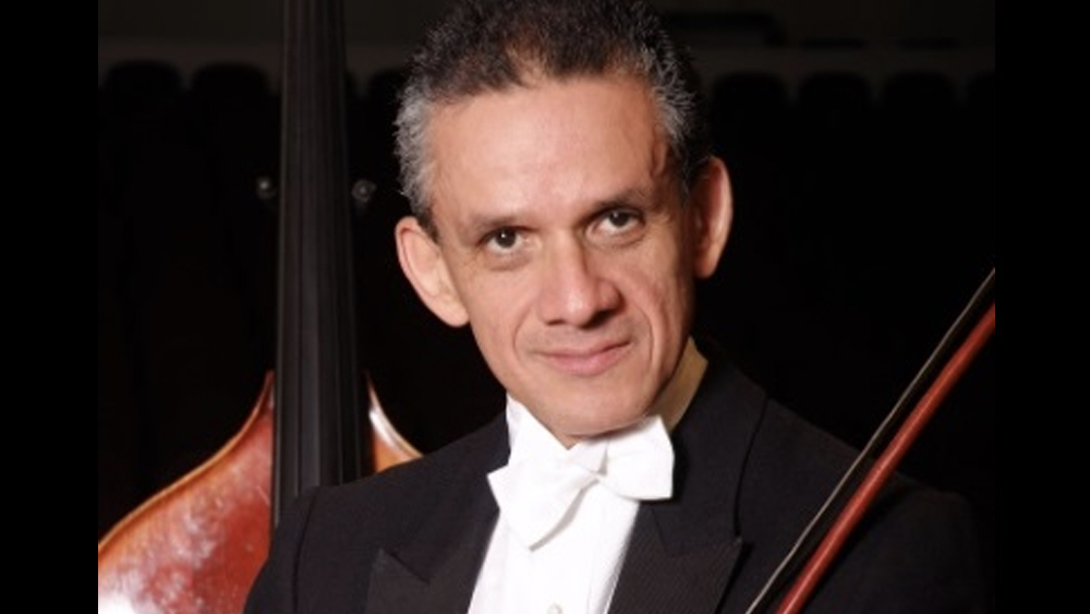 Headshot of Luis Gomez in a white bow tie with his contrabass behind him against a black background.