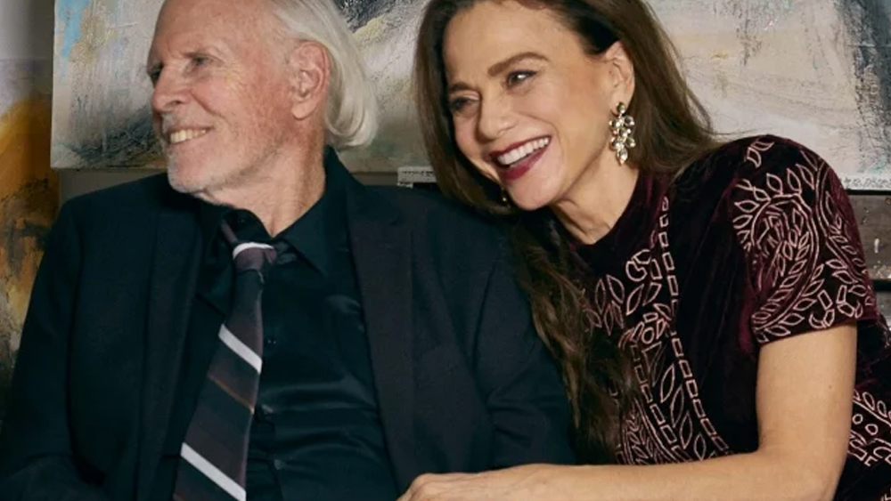 Image of an older smiling white man with a coat and tie in his 80s sitting next to a smiling woman in her 60s or 70s who is smiling and holding his arm. Both are looking off to the left.