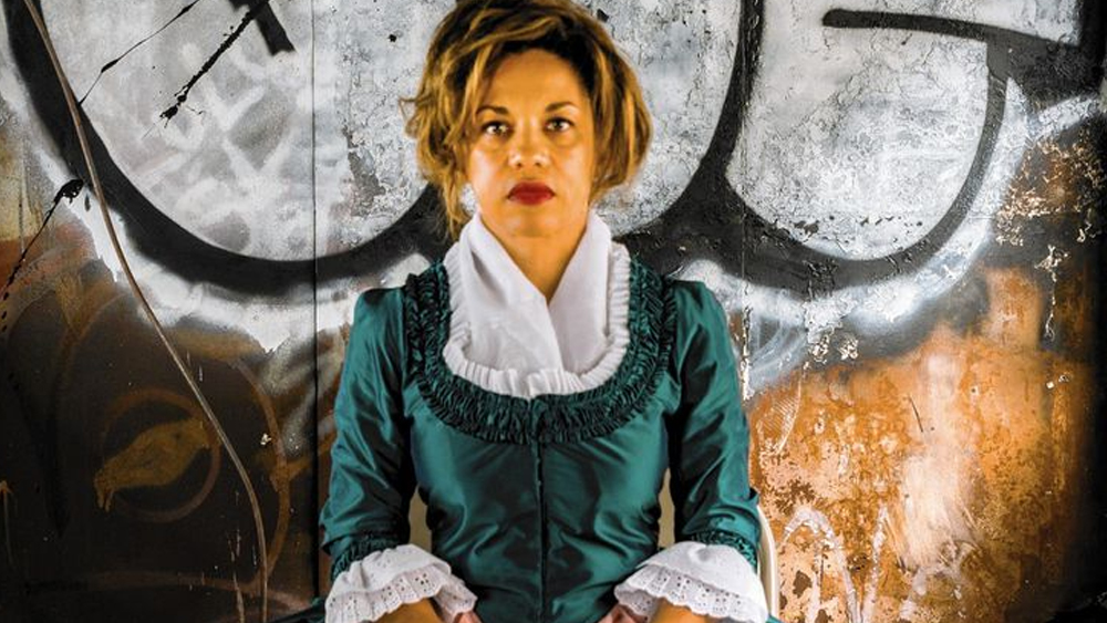 Image of Marielle, a light-skinned black woman wearing an 18C style dress in front of modern graffiti.