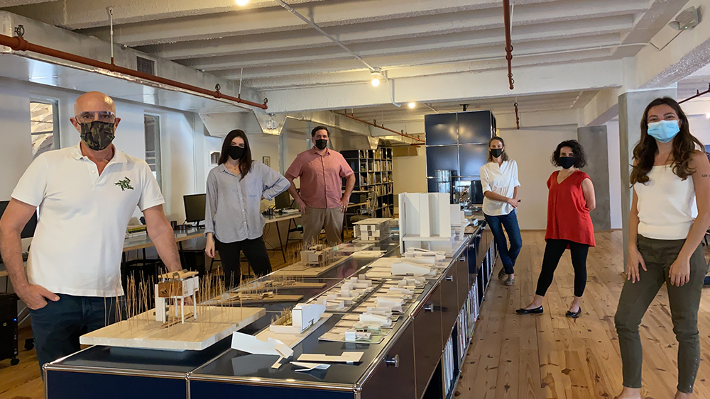Image of six people wearing masks and physically distance in an architecture office with wood floors and white beamed ceiling.  in the middle of the room is a long low cabinet with architectural models on top. No words.