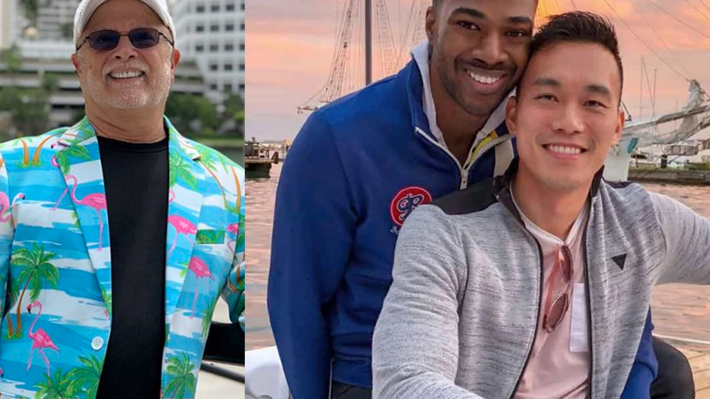 On the left George Neary standing with bright sports jacket with blue waves, green palms and pink flamingos printed on it.  On right Teraj a handsome young Black man smiles as he snuggles up with Barry, a handsome young Asian man on a pier with boats in the background at sunset.