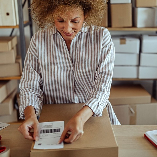 Woman entrepreneur putting a packing slip on a box.