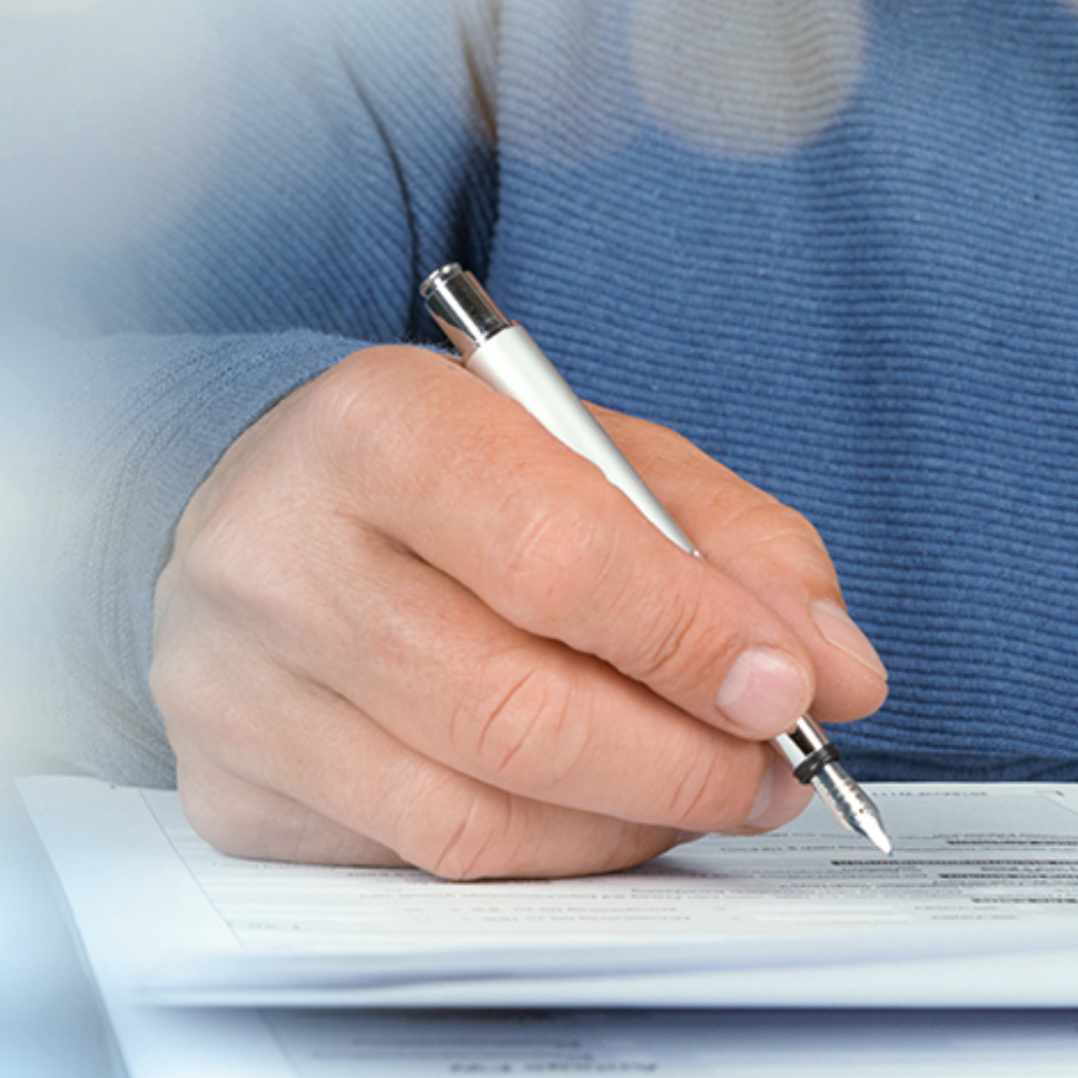 Person holding pen hovering over paper