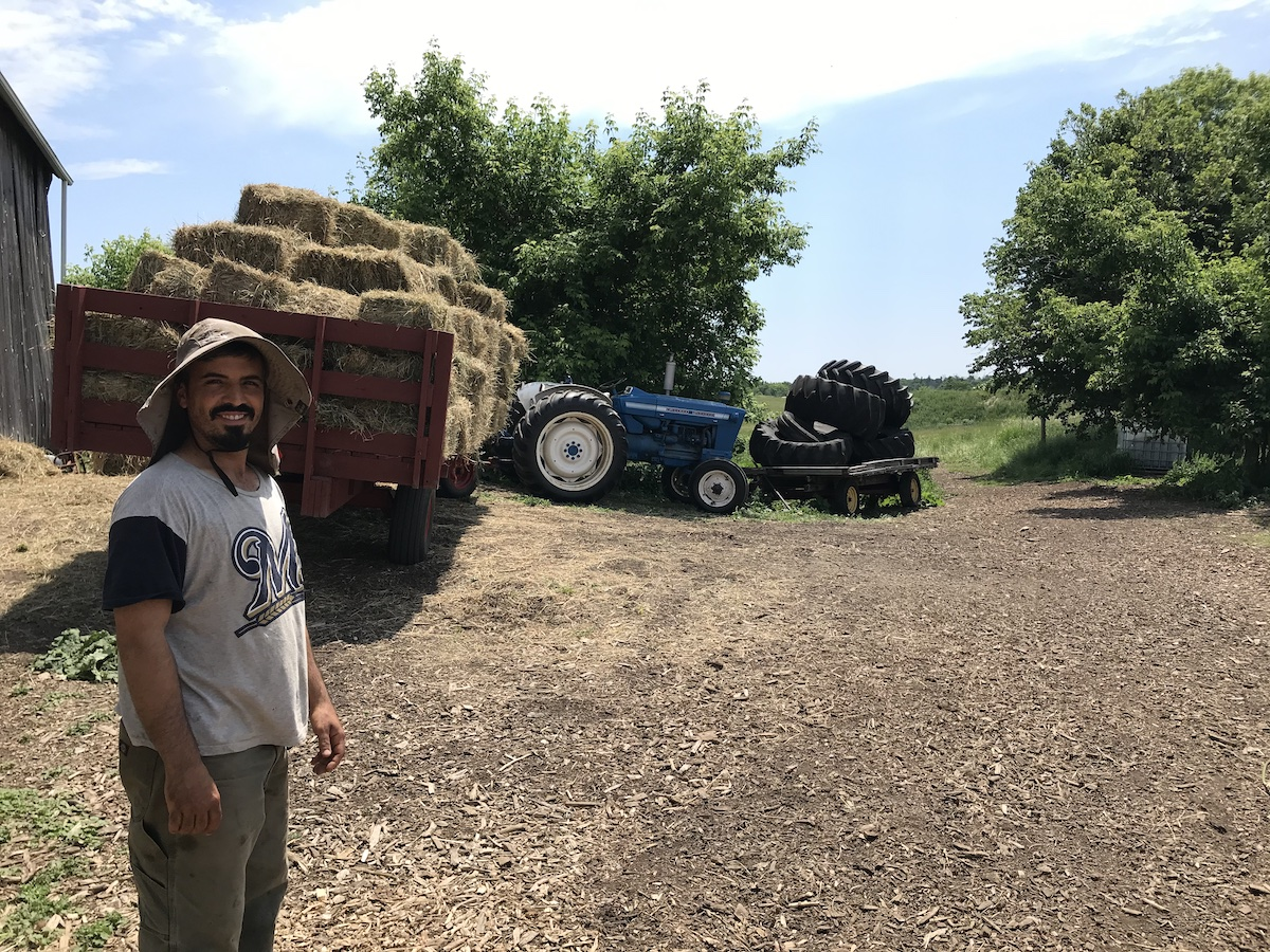 Antonio Gomes posing for a photo in front of hay bales and a tractor.
