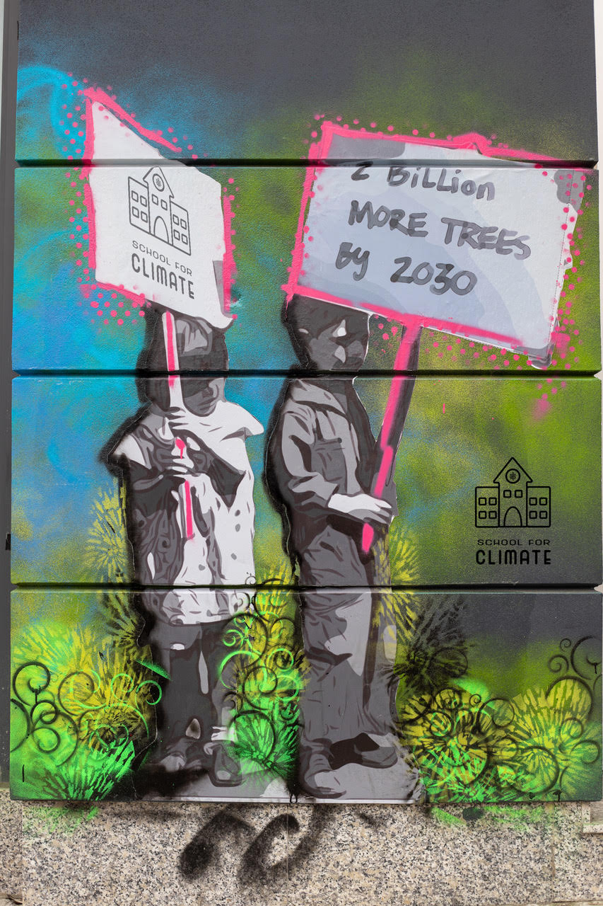 "Climate mural on the front of CSI Spadina: two kids holding up protest signs. One sign has the School for Climate logo, and the other says ""2 billion more trees by 2030."""