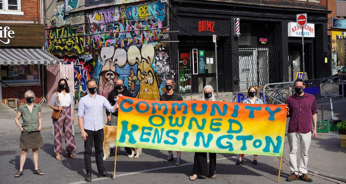 """Members of the Kensington Market Community land Trust stand outside of Brimz and Kensington Variety with a handmade sign that says """"Community Owned Kensington."""""""