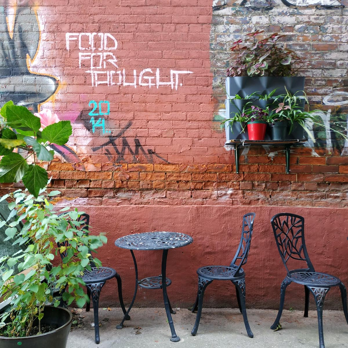 Plants and tables in front of a brick wall in the laneway just outside of CSI Annex.
