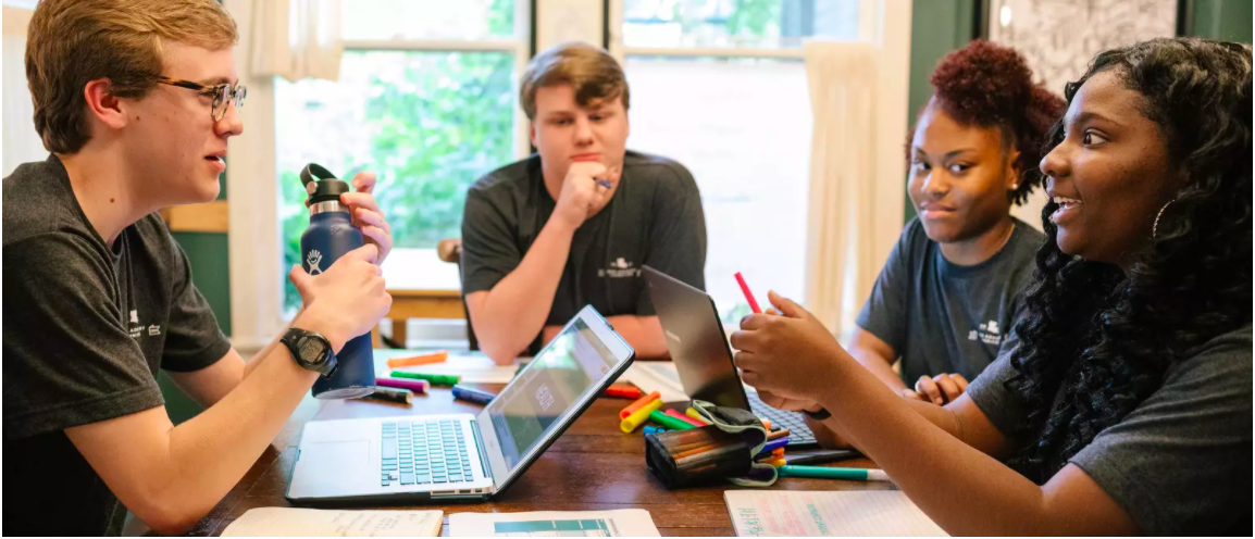 Four young adults discussing enthusiastically at a table with laptops, markers and paper in front of them.Image: Bryan Tarnowski | Inspired Story (Courtesy IYF)