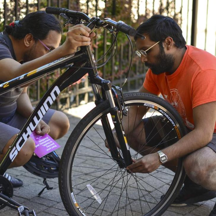 Two people kneeling next to a bicycle.