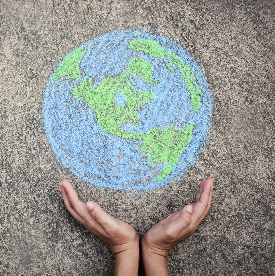 Hands cradling image of Earth drawn on concrete in chalk.
