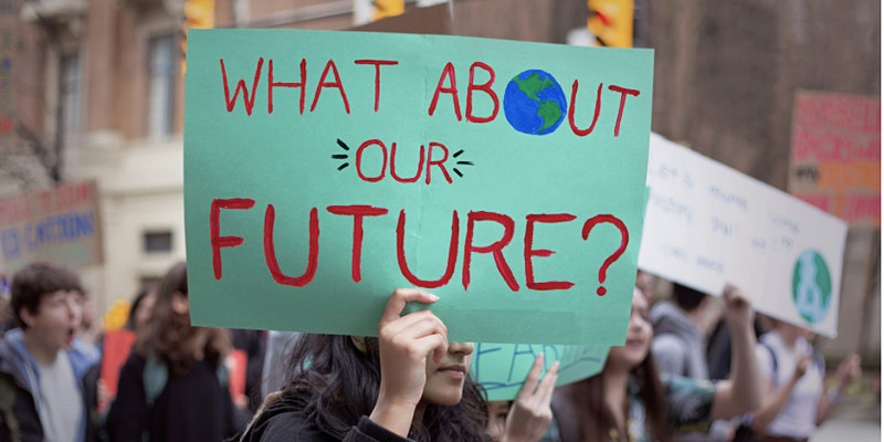 """What About Our Future?"" written on green construction paper being held up at a peaceful climate protest."