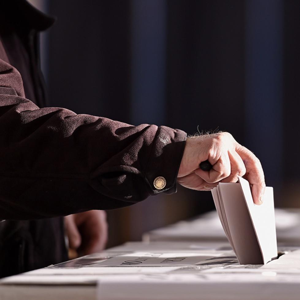 Person putting ballot into voting box.