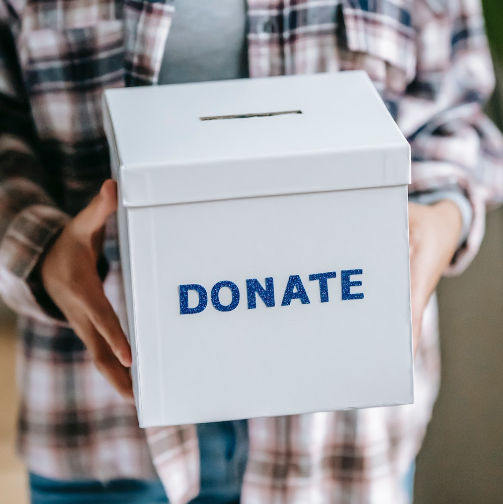 """Person in plaid shirt holding a white box that says """"Donate"""""""