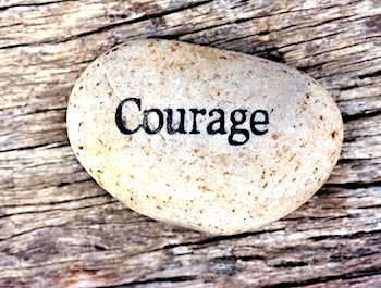 The word Courage carved on a stone