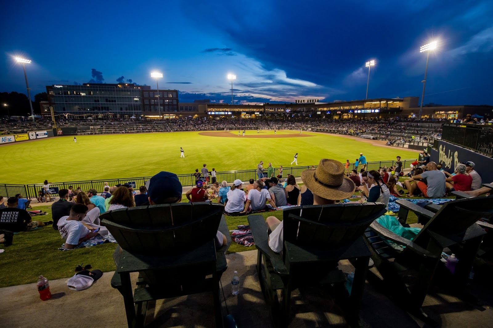 Photo of a crowd of people sitting in lawn chairs and on the grass in front of a baseball stadium at night.