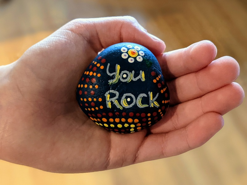 """child holding a rock with the words """"you rock"""""""