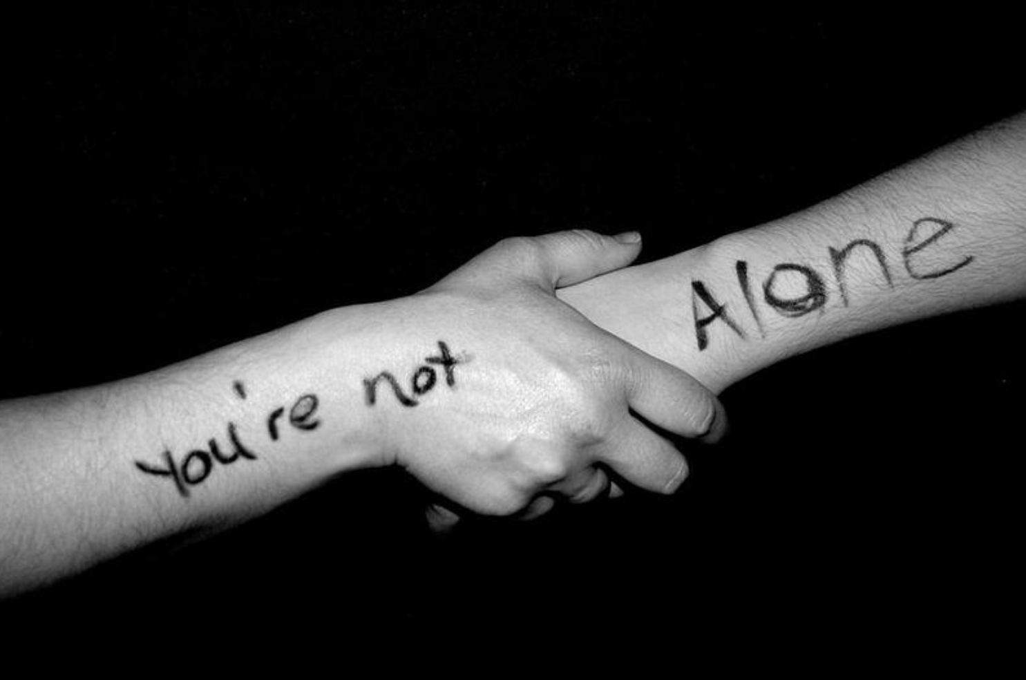 """two arms joined with the words """"you are not alone"""""""