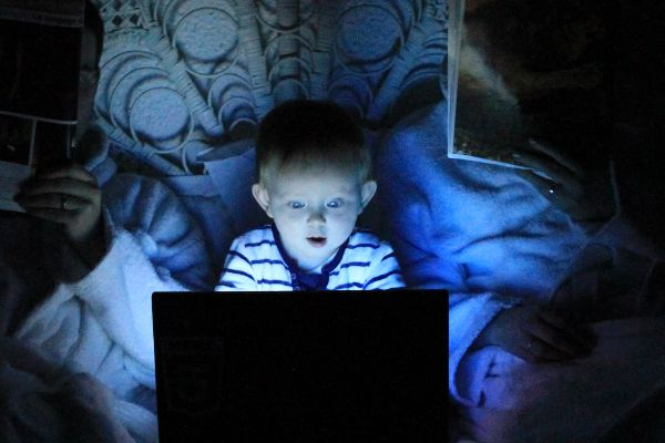 Small child with laptop looking interested