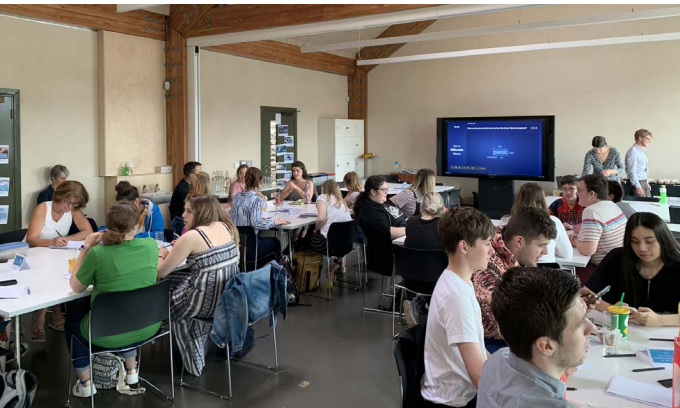 Many young people in a workshop, sitting at tables with pens and paper.