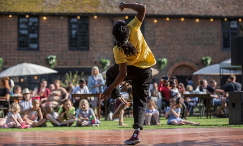Back of male dancer in action showing the audience watching in front of him. Outdoor event. Photo by Roswitha Chesher, courtesy of Greenwich Dance.