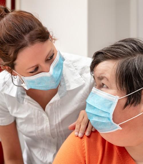 volwassen vrouw met handicap in bijzijn van haar begeleider, allebei met mondmasker op