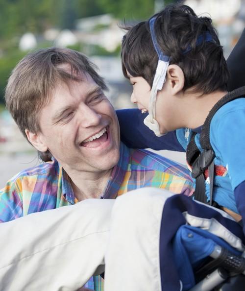 vader lacht naar jonge zoon in rolstoel