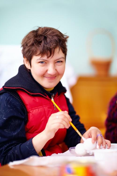 vrouw met handicap is creatief bezig (schilderen) in dagcentrum