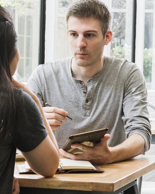 jonge man noteert antwoorden van een vrouw op een tablet